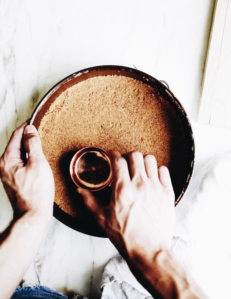 Pressing graham cracker crumbs into cheesecake pan