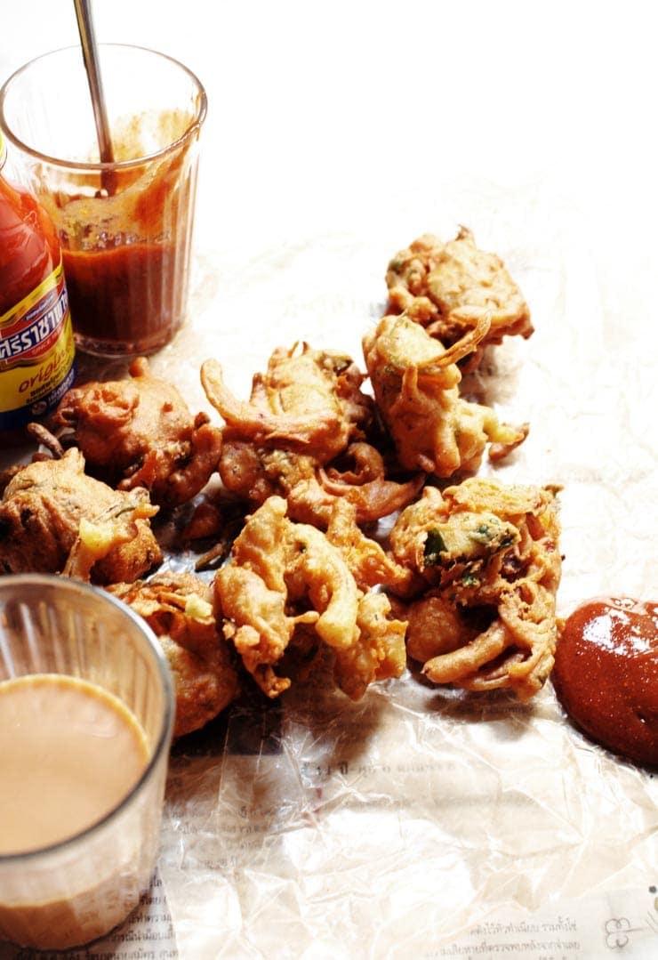 The best authentic crispy onion pakora recipe (pakoda) served with a delicious pakora sauce. Pakoras are delicious, easy, vegan, and gluten-free! | sophisticatedgourmet.com