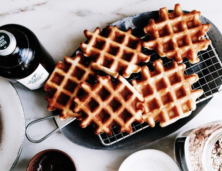 Homemade Belgian waffles on a platter with maple syrup on the side.